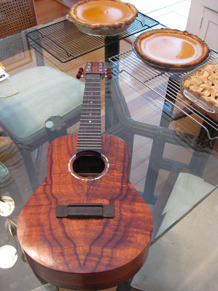 Nearly completed Koa ukulele on a glass table, with three holidays pies in the background